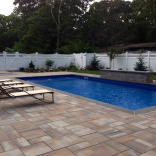 Inspiration for a mid-sized transitional backyard stone and rectangular pool remodel in New York