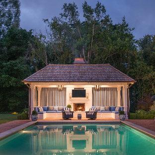 Ejemplo de casa de la piscina y piscina tradicional, grande, rectangular, en patio trasero, con adoquines de ladrillo