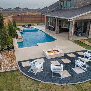 Immagine di una grande piscina american style rettangolare dietro casa con una vasca idromassaggio e pedane