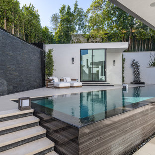 Inspiration for a mid-sized modern backyard tile and rectangular infinity pool house remodel in Orange County