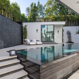 Ejemplo de casa de la piscina y piscina infinita, moderna, de tamaño medio, rectangular, en patio trasero, con suelo de baldosas