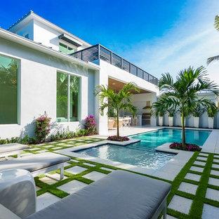 Ejemplo de piscinas y jacuzzis alargados, actuales, rectangulares, en patio trasero, con adoquines de hormigón