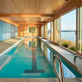 Diseño de piscina alargada, marinera, interior y rectangular, con losas de hormigón