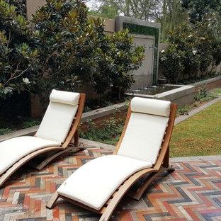 Modelo de piscina natural, ecléctica, rectangular, en patio lateral, con adoquines de ladrillo