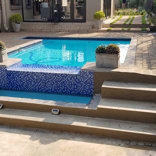 Diseño de piscina infinita, bohemia, rectangular, en patio delantero, con adoquines de hormigón