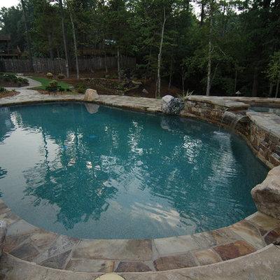 Hot tub - mid-sized rustic backyard stone and kidney-shaped hot tub idea in Atlanta