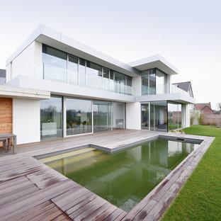 Moderner Pool hinter dem Haus in rechteckiger Form mit Dielen in Sonstige