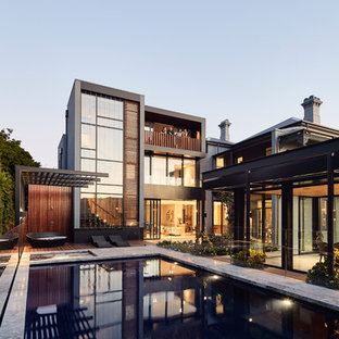 Large contemporary backyard rectangular aboveground pool in Melbourne with a pool house and natural stone pavers.