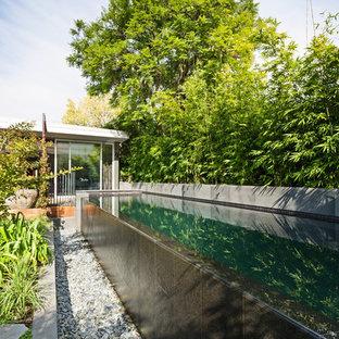 Imagen de piscina infinita, de estilo zen, de tamaño medio, rectangular, en patio trasero, con suelo de baldosas