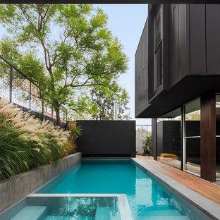 Ejemplo de piscina contemporánea, rectangular, en patio lateral, con entablado