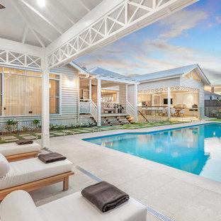 Ejemplo de casa de la piscina y piscina natural, retro, grande, rectangular, en patio trasero, con adoquines de piedra natural