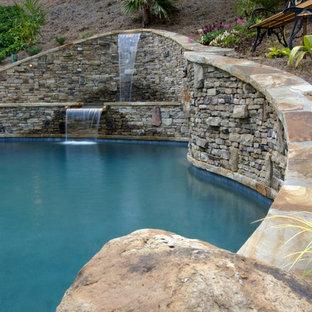 Foto de piscina con fuente natural, rústica, de tamaño medio, a medida, en patio trasero, con adoquines de ladrillo
