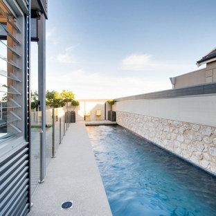 Imagen de piscina alargada, minimalista, grande, rectangular, en patio lateral, con suelo de hormigón estampado