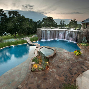 Photo of an expansive eclectic backyard custom-shaped natural pool in Oklahoma City with a water feature and natural stone pavers.