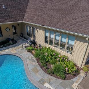 Foto de piscinas y jacuzzis alargados, clásicos, grandes, tipo riñón, en patio trasero, con suelo de baldosas