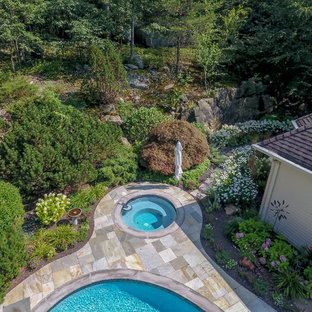 Large traditional backyard kidney-shaped lap pool in New York with a hot tub and tile.