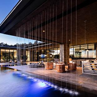 Ispirazione per un'ampia piscina a sfioro infinito moderna personalizzata dietro casa con una vasca idromassaggio e pavimentazioni in pietra naturale