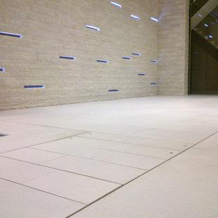 Modelo de piscina con fuente contemporánea, de tamaño medio, en forma de L y interior, con adoquines de piedra natural