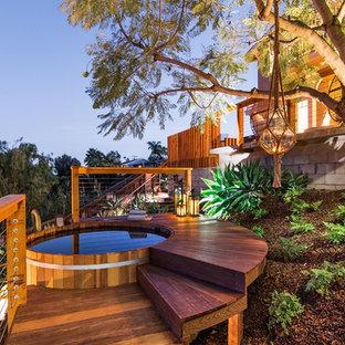 Ispirazione per una grande piscina contemporanea dietro casa con pedane e una vasca idromassaggio