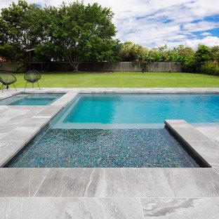 Exemple d'un grand couloir de nage arrière tendance rectangle avec un aménagement paysager autour d'une piscine et des pavés en pierre naturelle.