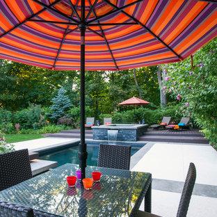 Diseño de piscinas y jacuzzis alargados, de tamaño medio, en forma de L, en patio trasero, con adoquines de piedra natural