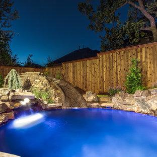 Imagen de piscina con tobogán natural, tropical, pequeña, a medida, en patio trasero