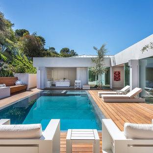 Modelo de piscinas y jacuzzis infinitos, actuales, rectangulares, en patio trasero, con entablado