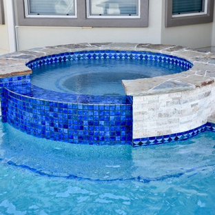 Modelo de piscinas y jacuzzis infinitos, tradicionales renovados, de tamaño medio, a medida, en patio trasero, con losas de hormigón
