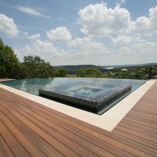 Esempio di una grande piscina a sfioro infinito design rettangolare dietro casa con una vasca idromassaggio e pedane