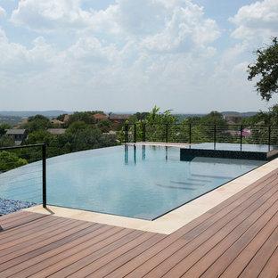 Idee per una grande piscina a sfioro infinito contemporanea rettangolare dietro casa con una vasca idromassaggio e pedane