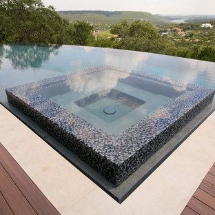 Idee per una grande piscina a sfioro infinito minimal rettangolare dietro casa con una vasca idromassaggio e pedane