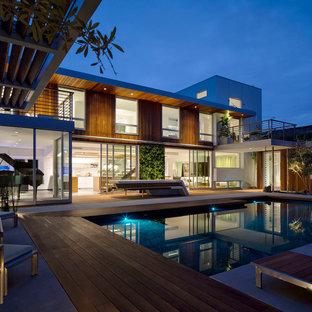 Ejemplo de piscina actual, grande, en patio, con entablado