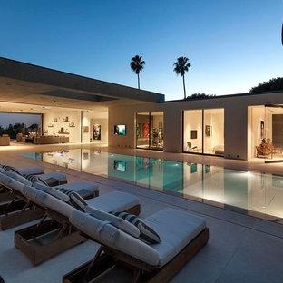 Inspiration för en mycket stor funkis rektangulär infinitypool på baksidan av huset, med spabad och betongplatta