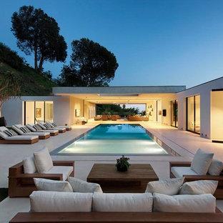 Imagen de piscina infinita, contemporánea, extra grande, rectangular, en patio trasero, con losas de hormigón