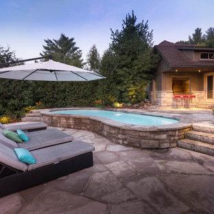 """Ispirazione per una piscina classica a """"C"""" di medie dimensioni e dietro casa con una dépendance a bordo piscina e pavimentazioni in pietra naturale"""