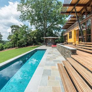 Modelo de piscina alargada, vintage, de tamaño medio, rectangular, en patio trasero, con adoquines de hormigón