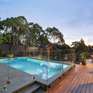 This is an example of a large transitional backyard custom-shaped lap pool in Melbourne with decking.