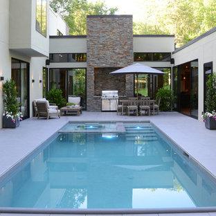 Exemple d'une grand piscine sur toit naturelle moderne rectangle avec du carrelage et un bain bouillonnant.