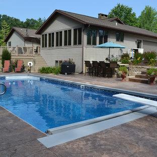Diseño de piscina alargada, tradicional, de tamaño medio, rectangular, en patio trasero, con losas de hormigón