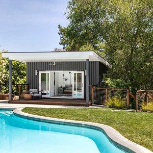 Ejemplo de casa de la piscina y piscina actual, de tamaño medio, a medida, en patio trasero, con losas de hormigón