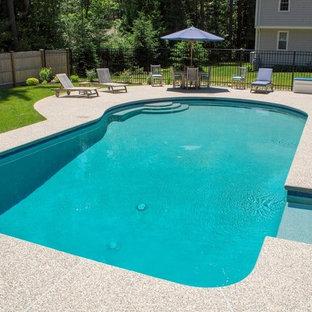 Modelo de piscina alargada, tradicional renovada, de tamaño medio, a medida, en patio trasero, con granito descompuesto