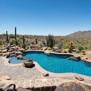 На фото: бассейны произвольной формы на заднем дворе в стиле фьюжн с фонтаном