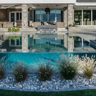 Foto de piscina con fuente infinita, clásica, de tamaño medio, rectangular, en patio delantero, con adoquines de piedra natural