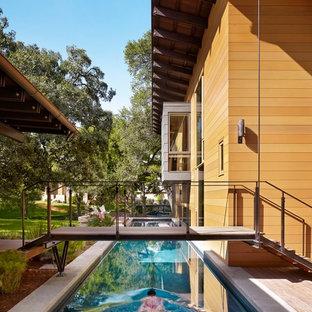Foto de piscina alargada, contemporánea, rectangular, en patio lateral