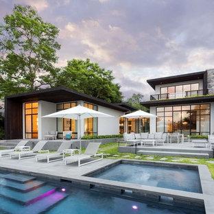 Esempio di un'ampia piscina monocorsia contemporanea rettangolare dietro casa con una vasca idromassaggio e pavimentazioni in cemento