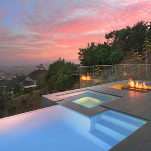 Exemple d'une petit piscine à débordement et arrière moderne sur mesure avec un bain bouillonnant et du carrelage.