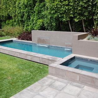 Imagen de piscina con fuente alargada, moderna, pequeña, rectangular, en patio trasero, con adoquines de hormigón