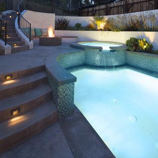 Foto de piscinas y jacuzzis naturales, tradicionales renovados, de tamaño medio, tipo riñón, en patio trasero, con losas de hormigón