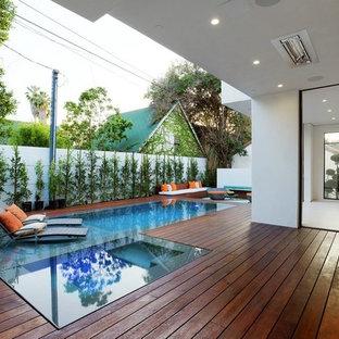 Immagine di una piscina a sfioro infinito minimalista rettangolare di medie dimensioni e dietro casa con pedane