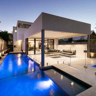 Modelo de piscina alargada, actual, de tamaño medio, en forma de L, en patio lateral, con suelo de hormigón estampado